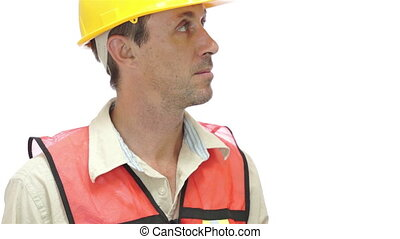 Male tradesman dressed in an orange safety vest and yellow hard hat turns to the camera and with a big smile passes an orange tape measure towards the viewer.