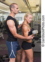 Male trainer assisting woman in gym