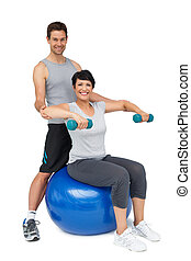 Male trainer assisting woman with dumbbells
