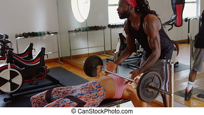 Male trainer helping female boxer to lift a barbell 4k - ...