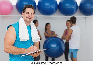 Male trainer holding clipboard with fitness class in...
