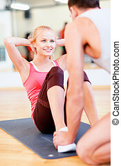 male trainer with woman doing sit ups in the gym