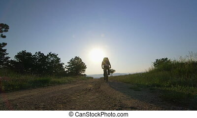 Male traveler cycling at sunrise