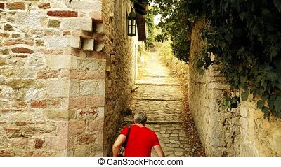 Male traveler in red tshirt walks in ancient Mediterranean...