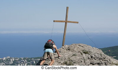 Male traveler with a backpack on his back reaches the top of...