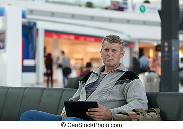 male traveler with the laptop uses a Wi-Fi with expectation...