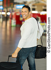 male traveller walking in airport with luggage