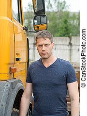Male trucker standing near his yellow truck.