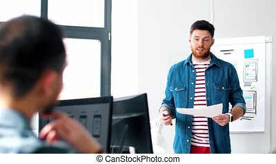 male ui designer showing user interface at office - user...