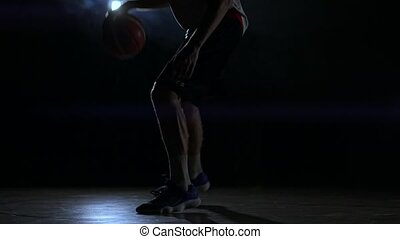 Male urban basketball player dribbles ball in crouched...