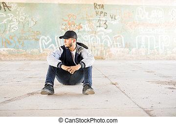 Male urban dancer taking a break