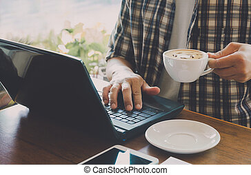 Male using a computer with coffee cup on wooden table.