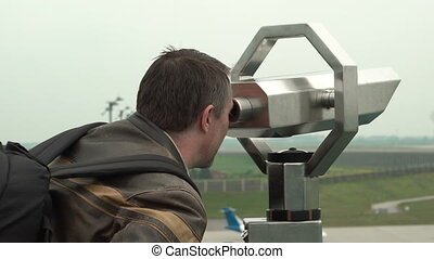 Male Using a Tower Viewer at an Airport
