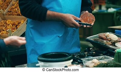 Male vendor shelling scallops at local seafood stall on the...