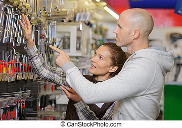 male vendor showing wrench to female customer in hardware shop