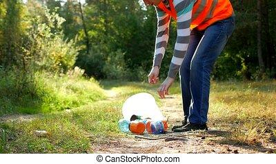 male volunteer cleaner in the signal orange vest cleans...