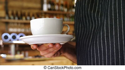 Male waiter holding a coffee cup in cafe 4k
