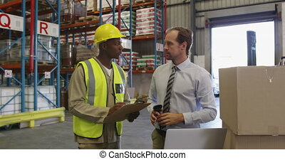 Male warehouse manager and warehouse worker in loading bay ...