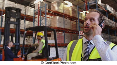 Male warehouse manager talking with headset in loading bay ...