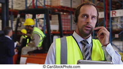 Male warehouse manager using headset and tablet 4k - Close ...