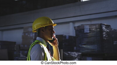 Male warehouse manager using phone 4k