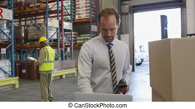 Male warehouse manager working in loading bay 4k - Front ...