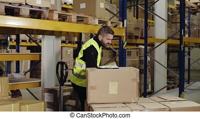 Male warehouse worker loading hand pallet truck. - Young...