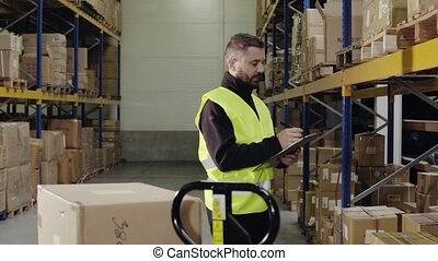 Male warehouse worker making notes. - Young male warehouse...