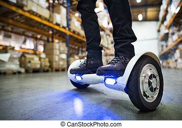 Male warehouse worker on hoverboard. - Unrecognizable man...