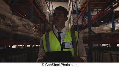 Male warehouse worker patrolling warehouse corridor at night...