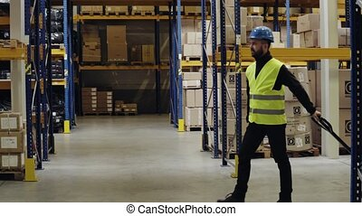 Male warehouse worker pulling a pallet truck. - Young male...