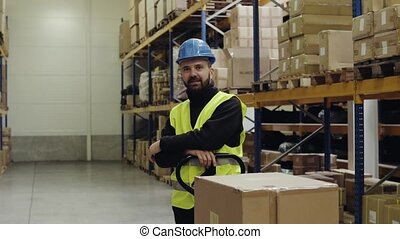 Male warehouse worker standing by pallet truck. - Young male...