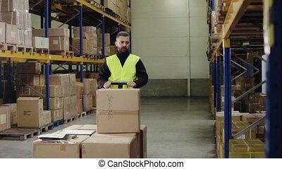 Male warehouse worker unloading boxes from pallet truck. -...