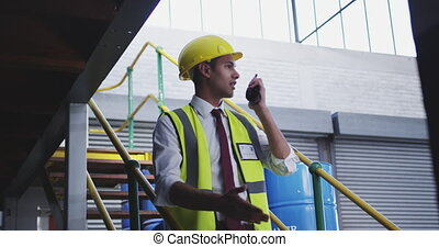Male warehouse worker using two-way radio 4k
