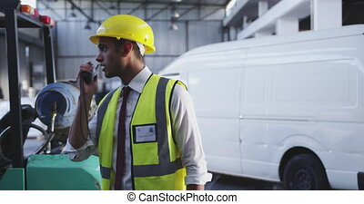 Male warehouse worker using two-way radio 4k - Close up side...