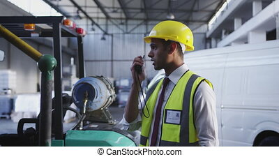 Close up side view of a young Asian male warehouse worker standing in a warehouse loading bay talking on a two-way radio. They are working in a freight transportation and distribution warehouse. Industrial and industrial workers concept 4k