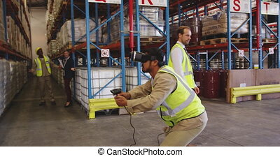 Male warehouse worker using VR headset and controller in ...