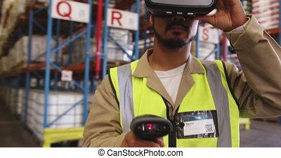 Male warehouse worker wearing VR headset in loading bay 4k...