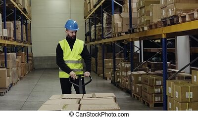 Male warehouse worker with a pallet truck. - Young male...