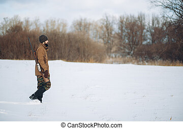 Male warm clothes walking on the field with hunting rifle