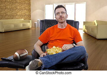 Male Watching Football with Snacks