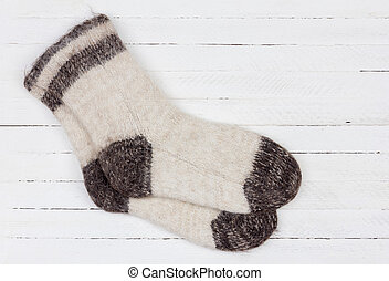 male white knitted dog fur socks on white wooden background close-up, top view