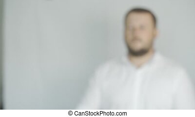 male with a beard throws up a ball on white background, concept of success, slow motion, soft focus
