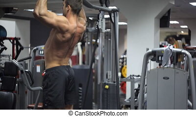 Male with an athletic build exercising on bar at gym. Pull-UPS this exercise is most often performed on horizontal bar working muscle groups a complex of muscles in arms mostly biceps, forearm and back. Wider grip hands on crossbar, more burden falls on broadest muscle of back narrower grip more ...