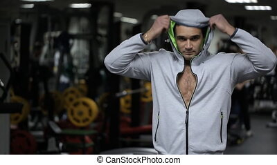 Male with an athletic build removes hood in gym.