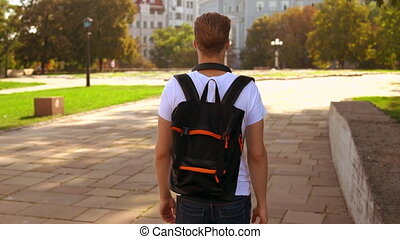 male with knapsack stroll in city - back view young man...
