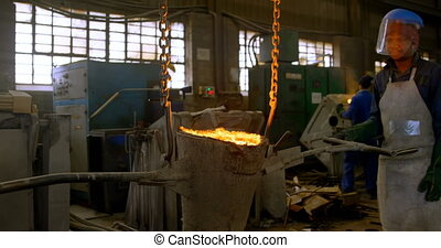 Male worker carrying molten metal in workshop 4k