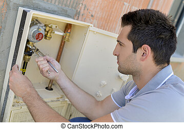 male worker checking the water meter