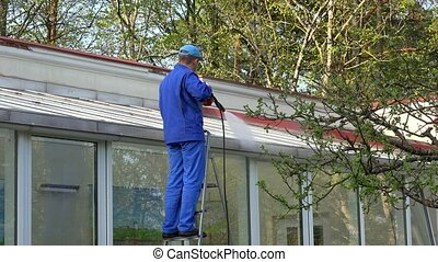 male worker clean window of glass house.