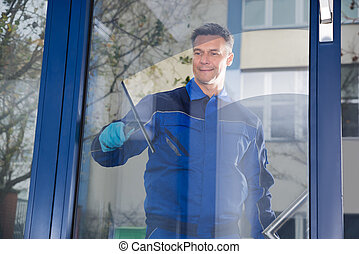 Male Worker Cleaning Glass With Squeegee - Happy mature male...